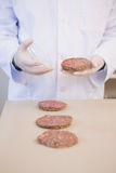 Scientist examining beefsteaks in petri dish Stock Photography