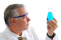 Scientist examining liquid in a beaker. Profile shot of a middle aged scientist examining a blue liquid in a beaker isolated over white. Horizontal format Royalty Free Stock Image