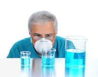 Scientist examining liquid in beakers Stock Images