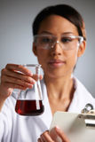 Scientist Examining Liquid In Flask Holding Clipboard Stock Photo
