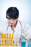 Scientist experimenting with yellow solutions Royalty Free Stock Photo