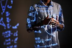Scientist explaining his mathematical calculations. Close-up of unrecognizable male scientist in shirt standing in dark room and gesturing hands while explaining royalty free stock photos