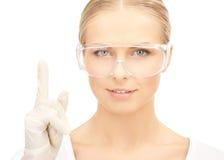 Scientist in eyeglasses holding finger up Stock Images
