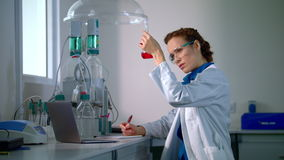 Scientist find a cure. Woman scientist looking at chemical liquid in lab flask stock footage
