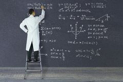 Scientist of genius writing mathematical formulas. Scientist of genius standing on a ladder writing complex mathematical formulas with white chalk on large Stock Images