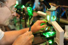Scientist with glass. Loupe configure  laser of microparticles Stock Photos