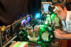 Scientist with glass demonstrate laser. Of microparticles, scientist in focus Royalty Free Stock Images
