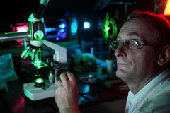Scientist with glass demonstrate laser. Of microparticles, side Stock Photo