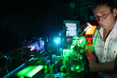 Scientist with glass demonstrate laser. Of microparticles, front Stock Image