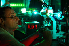 Scientist with glass demonstrate laser. Of microparticles near timer Royalty Free Stock Photos