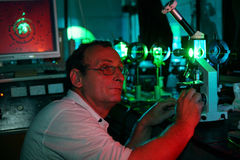 Scientist with glass demonstrate laser. Of microparticles in red lighting lab Royalty Free Stock Images