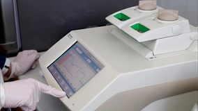 Scientist with gloved hand is programming DNA analysis in real-time PCR-cycler. Scientist with gloved hand is programming DNA analysis in real-time automatic stock video footage