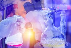 Scientist hand holding flask with distillation set with dropping funnels is separating the component substances from liquid mixtur. E and scientist looking Stock Images