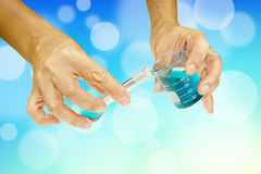 Scientist hand pouring blue liquid Stock Photos