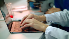 Scientist hand typing on laptop. Close up of female scientist hands on laptop stock video