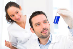 Scientist and his assistant working in a lab Stock Photos