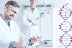 Scientist holding 3D printout. With other men standing behind stock photography