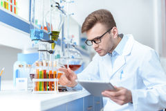 Scientist holding digital tablet and working with test tubes in lab royalty free stock photography