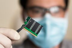 Scientist holding and examining damaged electrical component Stock Image