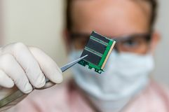 Scientist holding and examining damaged electrical component Royalty Free Stock Photography