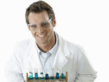 Scientist holding rack of test tubes, smiling, portrait, elevated view, cut out Royalty Free Stock Image