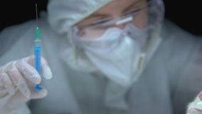 Scientist holding syringe with substance and test animal, developing medication