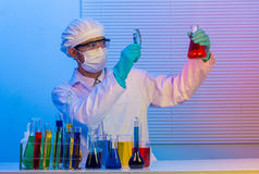 Scientist holding a test tube with magnifying glass Stock Photography