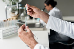 Scientist holding test tube with reagent while making experiment in lab Royalty Free Stock Image