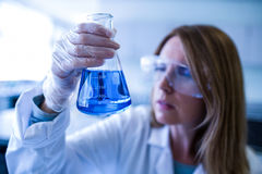 Scientist holding up beaker of chemical Stock Photos