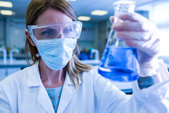 Scientist holding up beaker of chemical Stock Photo