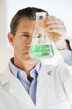 Scientist holding up jar of chemicals Stock Images