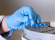 Scientist holds a chemical sample bottle. Scientist in blue gloves holds a chemical sample bottle Royalty Free Stock Photography