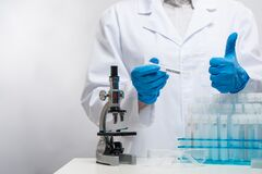 Free Scientist In Blue Protection Gloves Analyzing Covid-19 Vaccine With Microscope On Laboratory Room Background. Healthcare And Royalty Free Stock Images - 199408199