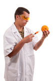 Scientist injecting GMO into orange Royalty Free Stock Photo