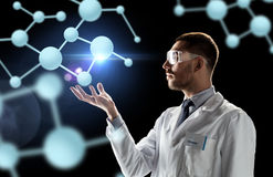 Scientist in lab coat and goggles with molecules Stock Images