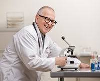Scientist in lab coat with microscope Stock Image