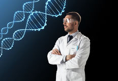 Scientist in lab coat and safety glasses with dna. Science, genetics and people concept - male doctor or scientist in white coat and safety glasses with dna stock images