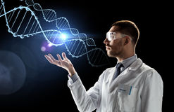 Scientist in lab coat and safety glasses with dna. Science, genetics and people concept - male doctor or scientist in white coat and safety glasses with dna Royalty Free Stock Images