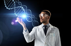 Scientist in lab coat and safety glasses with dna. Science, genetics and people concept - male doctor or scientist in white coat and safety glasses with dna Royalty Free Stock Photo