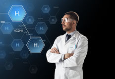 Scientist in lab goggles chemical formula. Science, future technology and chemistry concept - male doctor or scientist in white lab coat and safety glasses with royalty free stock photos