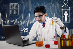 Scientist with laptop and chemical glassware Stock Photography
