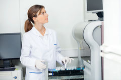 Scientist Loading Coagulation Analyzer With Test Royalty Free Stock Image