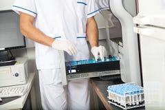 Scientist Loading Samples Into Analyzer Stock Photo