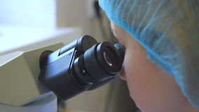 Scientist look at the microscope stock video