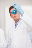 Scientist looking at beaker with blue fluid Royalty Free Stock Photo