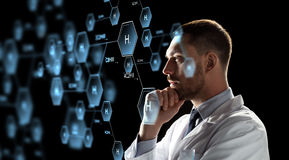 Scientist looking at chemical formula projection Stock Images