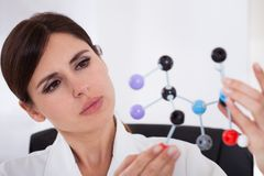 Scientist looking at dna molecular structure Stock Images