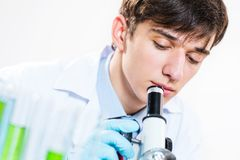 Scientist looking into a microscope Royalty Free Stock Photos