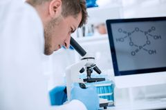 Scientist looking through a microscope in a laboratory. Close up.Scientist looking through a microscope in a laboratory Stock Photography
