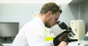 Scientist is Looking through Microscope and Writing Data on Tablet. stock footage